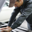 Mechanic working on car motor with hood open — Stock Photo