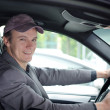 Handsome young man at wheel driving car — Stock Photo
