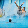 Young people having fun on water slides in aqua park — Stock Photo