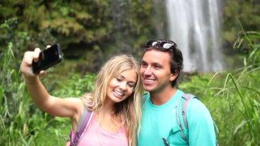 Junge glückliche paar unter selfie foto von wasserfall — Stockvideo