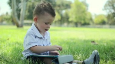 Young cute baby boy using phone touch screen at park. — Stock Video