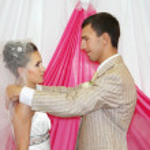 Happy groom raises veil to beautiful bride indoor at wedding — Stock Photo