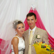 Happy groom with flowers and beautiful bride smile indoor at wed — Stock Photo