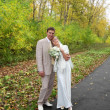 Young groom hugs his beautiful bride with roses in autumn park — ストック写真