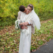 Young groom hugs his beautiful bride with roses and kisses neck  — Стоковая фотография