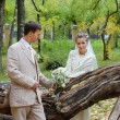 Happy young bride and groom stand neat to fallen old tree in aut — Stock Photo #28605455