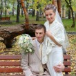Happy young bride and groom embrace at bench in autumn park — Stock Photo