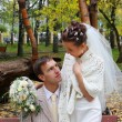 Happy bride and groom look at each other at bench in autumn park — Stock Photo