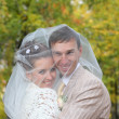 Happy smiling veil covered bride and groom embrace in autumn for — Stock Photo