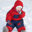 Little girl wearing warm jumpsuit sits on snow and eats snow at — Stock Photo #28605699
