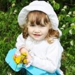 Beautiful little girl wearing white panama holds yellow dandelio — Stock Photo #28606153