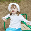 Stock Photo: Llittle girl wearing white panamrides on small carousel at pla