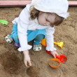 Little cute girl wearing white panama plays in sandbox — Stock Photo