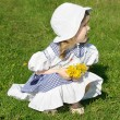 Beautiful little girl wearing dress with yellow dandelions sits — Stock Photo #28606477