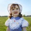 Happy little girl wearing dress and white panama stands on green — Stock Photo #28606609