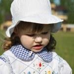 Beautiful little girl wearing dress and white panama looks down — Stock Photo #28606611