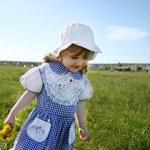 Happy little girl wearing dress and white panama walks on green — Stock Photo #28606659