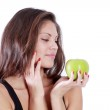 Beautiful brunette girl look at green apple isolated on white ba — Stock Photo