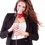 leende kvinna i kostym rymmer röd ros isolerad på vita bak — Stockfoto