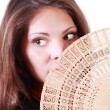 Young woman looks away and hides her mouth by fan isolated on wh — Stock Photo
