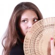 Young woman looks up and hides her mouth by fan isolated on whit — Stock Photo