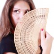 Beautiful girl looks away and hides her mouth and nose by fan is — Stock Photo