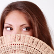 Beautiful brunette girl peeks out from behind fan and looks away — Stock Photo