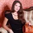 Beautiful smiling girl in short black dress with handbag sits on — Stock Photo