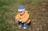 Little girl wearing orange jacket sits and plays with fir cones — Stock Photo