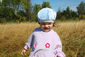 Happy little beautiful girl runs in dry grass on field at summer — Stock Photo