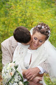 Groom hugs his beautiful bride with roses and kisses neck in aut — Stock Photo