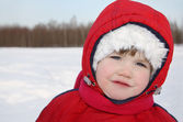 Little girl stands near forest at winter and looks into camera — Stock Photo
