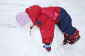 Little girl wearing warm jumpsuit lies on big snowball — Stock Photo