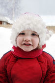 Cute little girl wearing warm clothing stands near home and smil — Stock Photo