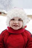 Schattig klein meisje dragen van warme kleding staat in de buurt van huis en smil — Stockfoto