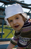 Cute little girl wearing white panama climbs on playground and l — Stock Photo