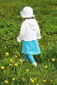 Back of little girl wearing white blouse walking on green field — Stock Photo