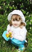 Beautiful little girl wearing white panama holds yellow dandelio — Stock Photo