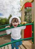 Cute little girl wearing white blouse stands on playground and l — Stock Photo