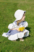 Beautiful little girl wearing dress with yellow dandelions sits — Stock Photo