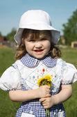 Beautiful little girl wearing dress holds yellow dandelions and — Stock Photo