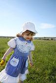 Happy little girl wearing dress and white panama walks on green — Stock Photo