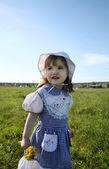 Happy little girl wearing dress looks into distance on green fie — Stock Photo