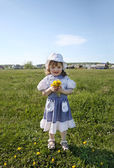 Happy little girl wearing dress holds yellow dandelions on green — Stock fotografie