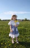 Happy little girl wearing dress holds yellow dandelions on green — Stock Photo