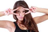 Close-up da jovem mulher olha através de dois sinais de paz isolado — Foto Stock