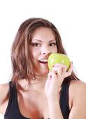 Beautiful smiling girl bites fresh green apple isolated on white — Stock Photo