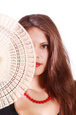 Beautiful girl looks at camera and half of her face by fan isola — Stock Photo