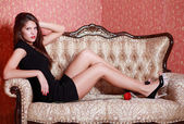 Beautiful girl in short black dress with red rose sits on vintag — Stock Photo