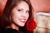 Hermosa chica feliz sostiene rosa cerca de cara roja y mira c — Foto de Stock